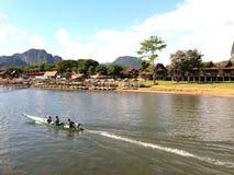 Turystyczny obsiadanie i podróżowanie długą ślad łodzią na rzece viewing górze i, niebieskie niebo z chmurami, lokalny wioska brz fotografia royalty free