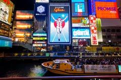 Turystyczny odprowadzenie w noc zakupy ulicie przy Dotonbori w Osaka, Japonia Zdjęcie Royalty Free