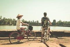 Turystyczny pary kolarstwo w Angkor ?wi?tyni, Kambod?a Angkor Wat g??wna fasada odbija? na wodnym stawie Eco turystyki ?yczliwy p zdjęcie stock