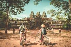 Turystyczny pary kolarstwo wokoło Angkor świątyni, Kambodża Ta Keo budynku ruiny w dżungli Eco życzliwa turystyka podróżuje, tonu zdjęcie stock