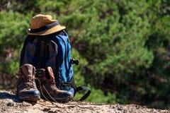 Turystyczny plecak, wycieczkujący buty i kapelusz na haliźnie w sosnowym lesie Zdjęcie Royalty Free