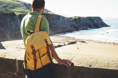 Turystyczny podróżnik z żółtą plecak pozycją na zieleń wierzchołku na górze, wycieczkowicza widok od tylny patrzeć na  fotografia stock