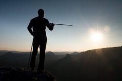 Turystyczny przewdonika przedstawienie prawy sposób z słupem w ręce Wycieczkowicz z sporty plecaka stojakiem na skalistym widoku  zdjęcia royalty free