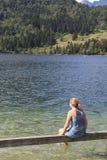 Turystyczny relaksować na ławce na jeziornym Bohinj, sławny miejsce przeznaczenia nie daleko od jeziora Krwawiącego Obrazy Royalty Free