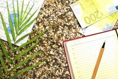 Turystyczny temat, piaskowata plaża, kompas, pieniądze, notatnik z fontanny pióra rośliną fotografia stock