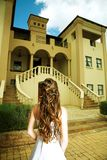 Tuscan bride. Bride in A-line dress and dark long curly hair standing with her back on the background of a Tuscan house stock photos