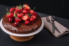 Tuscan chocolate cake with strawberries and cherries. On dark background Stock Photography