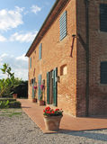 Tuscan farmhouse. Brick Tuscan farmhouse with shutters and tile patio Stock Photos