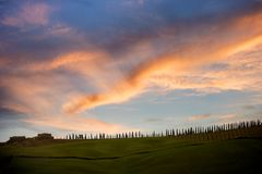 Tuscan hill with row of cypress trees and farmhouse ruin at sunset. Tuscan landscape. Italy. The Tuscan landscape, depicted in countless works, has been built by stock photos