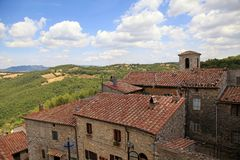 Tuscan hills and roofs of old houses in the Italian village, Tuscany, Italy. Beautiful landscape of the Tuscan hills and roofs of old houses in the Italian royalty free stock image