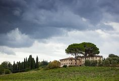 Tuscan hillside panorama with cloudy sky and typical local habit. Ation royalty free stock image