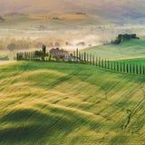Tuscan hus i kullarna bland cypressträden Royaltyfri Fotografi