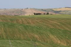 Tuscan kullebygd, med ett litet lantligt hus Royaltyfri Foto