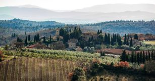 Tuscan landscape with cypress, trees and ancient buildings. Tuscan landscape and country road with cypress, trees and ancient buildings. Tuscany region in Italy Stock Photos