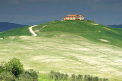 Tuscan landscape with farmhouse. On the hill. Storm dark sky in the background royalty free stock photo