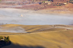 Tuscan landscape in the fog, Montepulciano (Italy). Agricultural land between Montepulciano and Arezzo (Tuscany, Italy Stock Photography