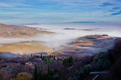 Tuscan landscape in the fog, Montepulciano (Italy). Agricultural land between Montepulciano and Arezzo (Tuscany, Italy Royalty Free Stock Photography