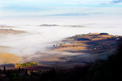 Tuscan landscape in the fog, Montepulciano (Italy). Agricultural land between Montepulciano and Arezzo (Tuscany, Italy Royalty Free Stock Photo
