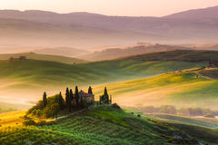 The Tuscan Landscape. Tuscan morning in Val d'Orcia, landscape with cypress trees, farmhouse, mist and hills Stock Photography