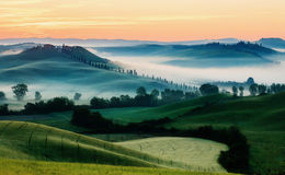 Tuscan Landscape in Sunrise Light. Tuscan fields in yellow sunrise light with old farm, Val d'Orcia royalty free stock photography