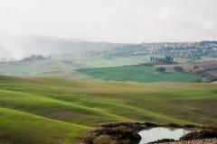 Tuscan landskap med gröna Rolling Hills i en dimmig dag, Tuscany, Italien royaltyfria foton