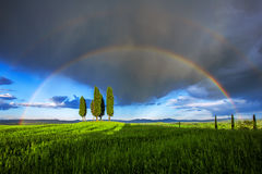 Tuscan rainbow. Typical tuscan landscape in the Orcia valley with a group of cypress trees surrounded by a double rainbow stock photos