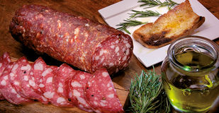 Tuscan salami, olive oil with rosemary and toast for typical Ita Stock Photos