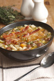 Tuscan soup. Delicious Tuscan soup with crispy bacon and beans royalty free stock image