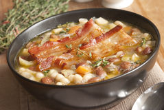 Tuscan soup. Delicious Tuscan soup with crispy bacon and beans Stock Images