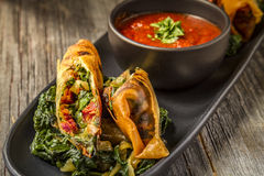 Tuscan Spring Rolls with Marinara Sauce. Tuscan spring rolls with sundried tomatoes, spinach, red onions, fontina cheese in wonton wrappers with bowl of marinara stock photo