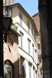 Old houses in a Tuscan street, Italy. Old terraced houses with shutters and balconies in a Tuscan street, Italy.  Full sun with shadow and blue sky Stock Images