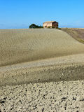 Tuscan style farm villa. Typical Tuscan house with plowed fields in autumn near Pienza in the Val d'Orcia in Tuscany, Italy Royalty Free Stock Photo