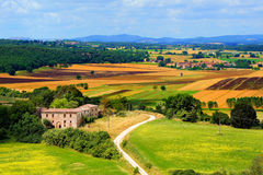 Tuscan view. View over the colorful fields of Tuscany with traditional farm house, Italy Royalty Free Stock Image
