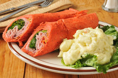Tuscan wrap sandwich. Wrap sandwich with ham, pepperoni, salami and romaine lettuce royalty free stock image