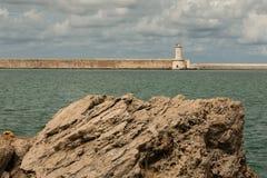 Tuscany Coastline: White Lighthouse Tower, Cliffs and Stone Jetty near Sea, Italy stock photography