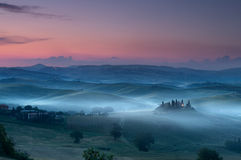 Tuscany before dawn. Tuscany just before dawn at San Quirico d'Orcia with view on Belvedere house in darkness and mist stock photo