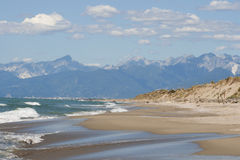 Tuscany deserted sand beach and mountains landscape Royalty Free Stock Photo