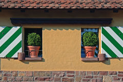 Tuscany facade. Tuscan courtyard front with flowerpots und painted shutters Stock Photography