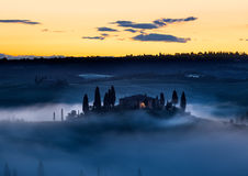 Tuscany farmhouse in morning mist with yellow skies, Val d'Orcia Royalty Free Stock Image