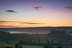 Tuscany farmhouse with vibrant sky at dawn, Val d'Orcia, Italy Stock Photos
