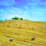 Tuscany, farmland on hill top, hay rolls and harvested green fields. Val d Orcia, Italy. Stock Images
