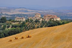 Tuscany, Italy. Houses on the hills of Tuscany in Italy. Hay rolls on the fields Stock Image