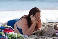 TUSCANY , ITALY 17 JULY 2018 : a woman uses her smartphone on the beach by the sea on vacation. TUSCANY , ITALY 17 JULY 2018 : a woman uses her smartphone stock images