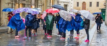 Umbrellas in the rain. Tuscany, Italy - May 6, 2017: People huddle with rain ponchos and umbrellas Stock Image