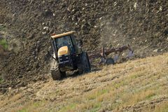 Crawler tractor plows the field. TUSCANY, ITALY - SEPTEMBER 23, 2017: Crawler tractor plows the field Royalty Free Stock Photography