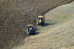 Two caterpillar tractors are working in the field Stock Images