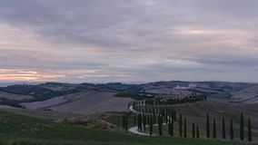 Sunset over vineyard fields and windy roads with cypress trees in Tuscany Italy. 4K time-lapse stock video footage