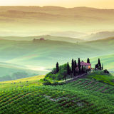 Tuscany, Landscape. A beautiful country house with the tuscan landscape in background, hills, cypress, olive trees Stock Photo