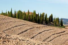 Tuscany landscape. Field, farm house among cypress trees. Italy Royalty Free Stock Photo