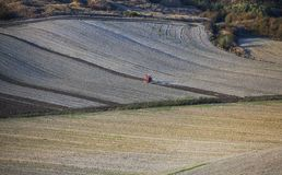 Tuscany - Landscape panorama, hills and meadow. Tractor on a field in Tuscany area of Italy during autumn Royalty Free Stock Images